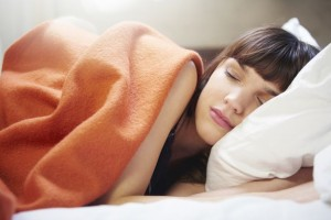 young Woman-sleeping orange blanket